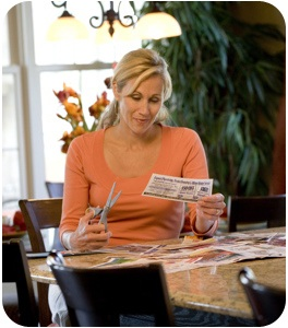 A woman clipping coupons at a table